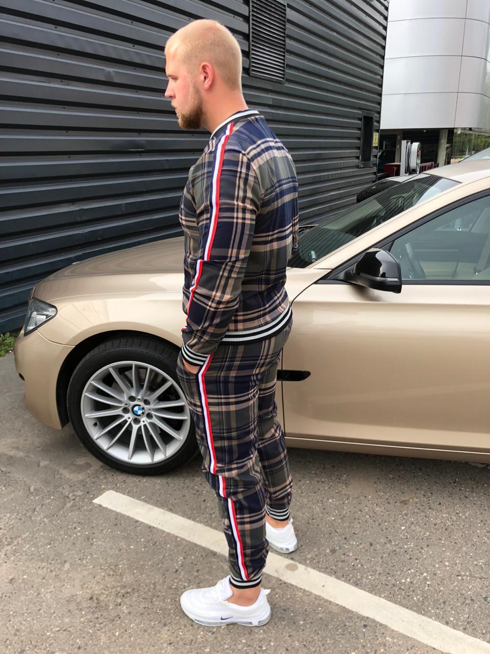 Мужской спортивный костюм из джентльменов на фоне машины